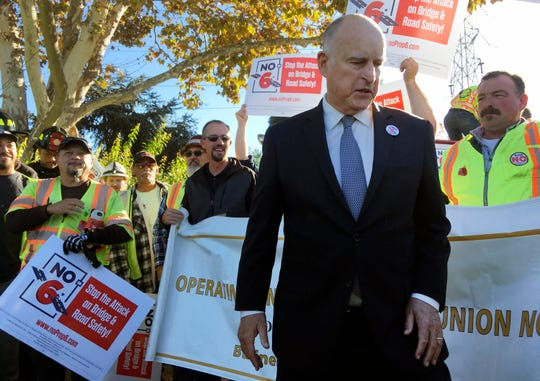 Gov. Jerry Brown joins a rally on behalf of a campaign against a repeal of the gas tax on Friday in Palo Alto. Proposition 6, would repeal an increase in gas tax and vehicle fees for transportation projects in California.