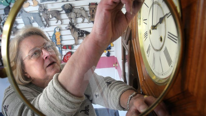 Kathy Faulls adjust a clock for a time change in this 2008 file photo.