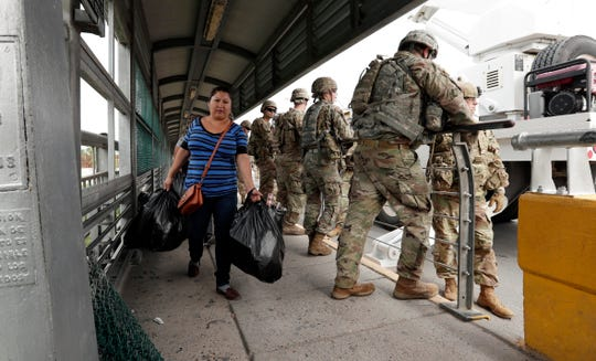 Pedestrians pass members of the U.S. military working to place razor wire along the U.S.-Mexico border on the McAllen-Hidalgo International Bridge on Friday in McAllen, Texas.