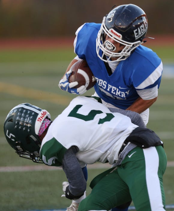 Dobbs Ferry's Thomas Ritch (21) tries to get around Woodlands' Tashaan Lewis (5) on a first half run  during the Section 1 Class D championship game at Mahopac High School Nov. 3,  2018.