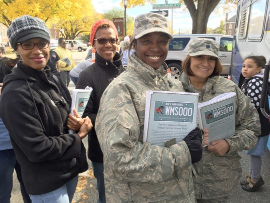 Jennifer Linton of Dover, Valerie Watson of Dover, Maj. Estelle Murray of Middletown, and Lt. Col. Liza Orlando of Milford wait in line at the Department of Motor Vehicles mobile station Saturday to receive their Delaware Women's Military Service license plates.