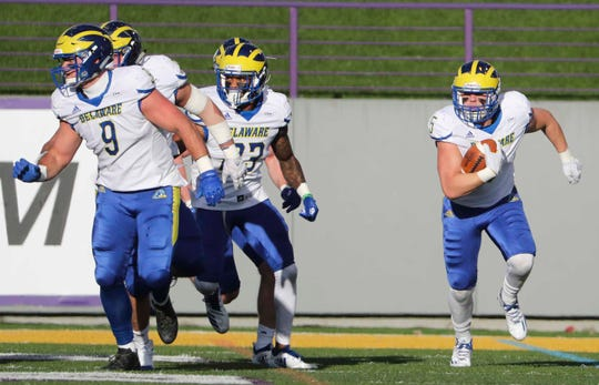 Delaware linebacker Charles Bell (right) has a cluster of blockers, including Troy Reeder (9) and Nasir Adderley (23) as he returns an interception in the first quarter at Albany in 2018.