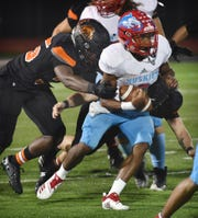 Hirschi quarterback Nate Downing (6) is hit by multiple Springtown defenders in second quarter action Friday night in Springtown.