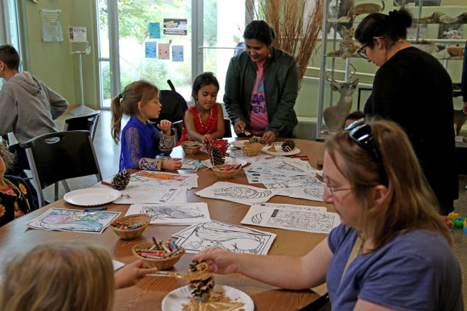 Kids and their parents cover acorns with peanut butter to make a bird feeder Saturday, Nov. 3, 2018, at the River Bend Nature Center.
