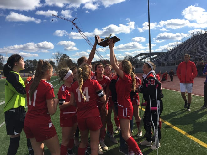 Rosecrans players hold aloft their first-ever Division III regional championship trophy, after beating Alexander 1-0 in double overtime Saturday at Logan Chieftain Stadium.