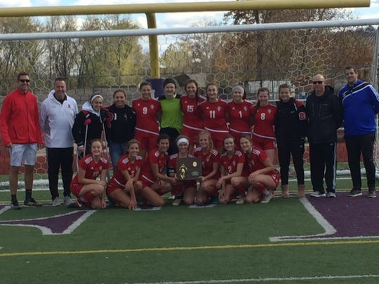 The Rosecrans girls soccer team poses with its first-ever Division III regional championship trophy, after beating Albany Alexander 1-0 at Logan Chieftain Stadium.