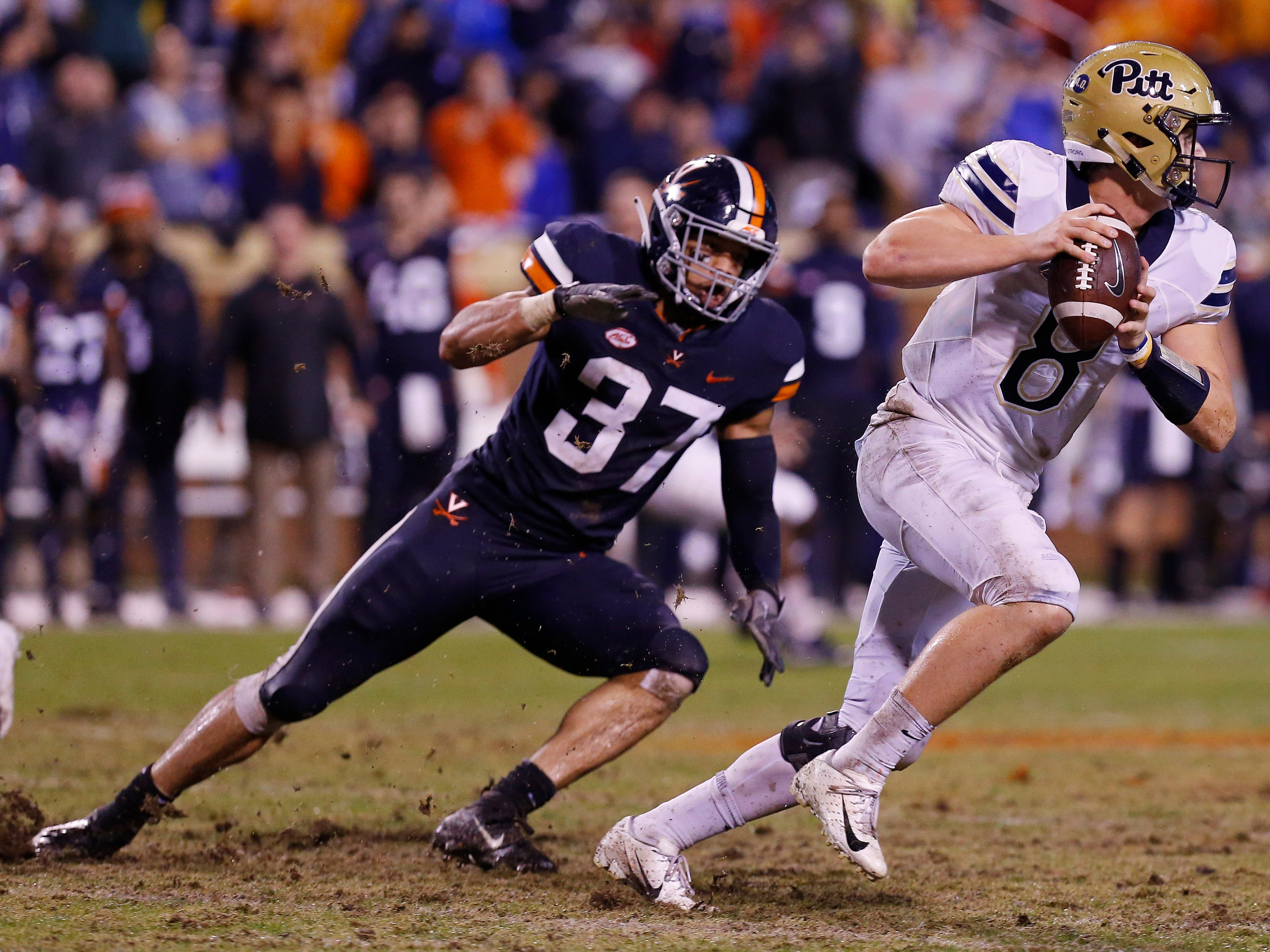Pittsburgh quarterback Kenny Pickett scrambles with the ball past Virginia  linebacker Jordan Mack (37) in the second quarter at Scott Stadium.
