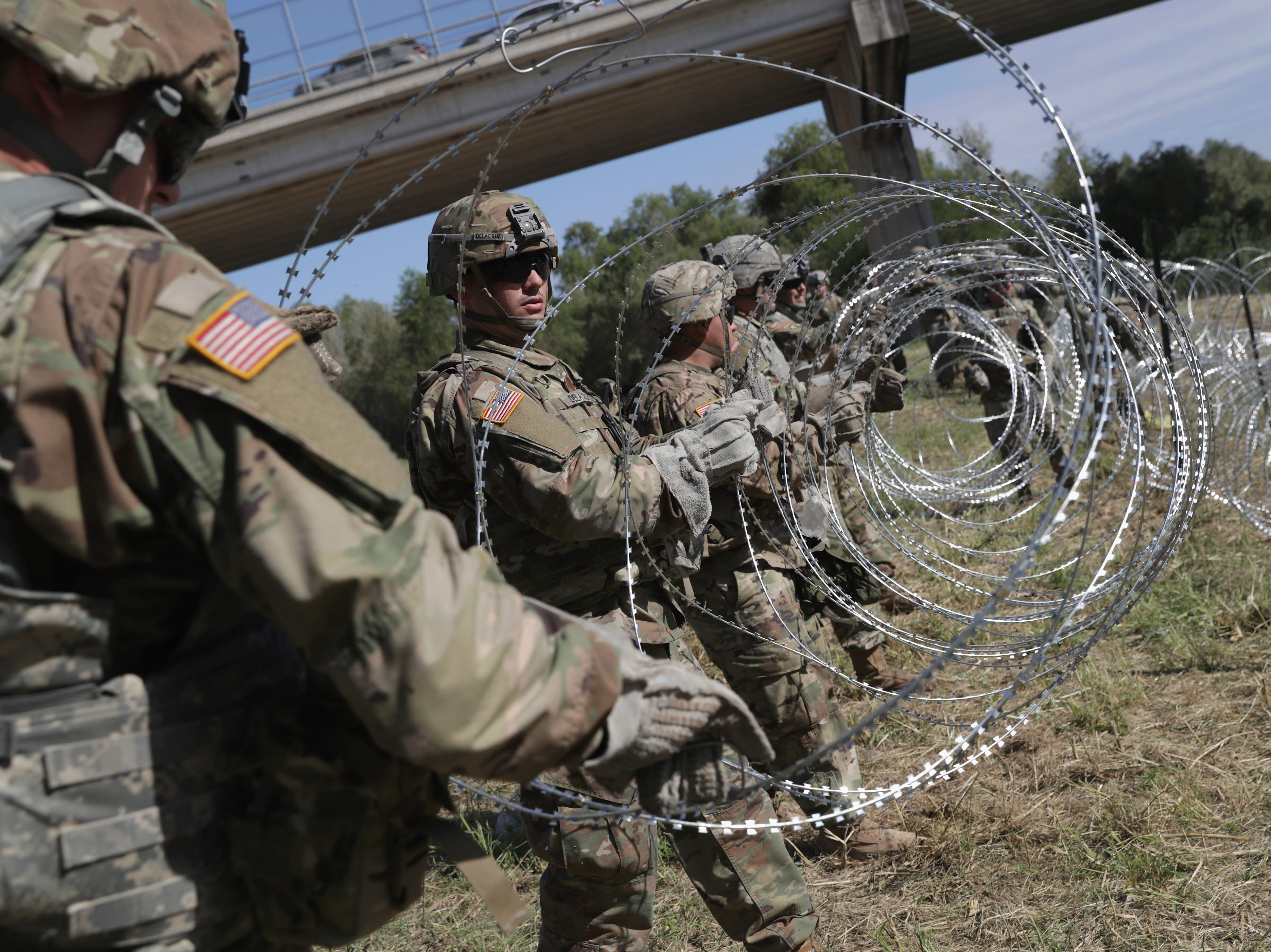 U.S. Army active duty troops from Ft. Riley, Kansas, 97th MP Battalion install protective wire along the Rio Grande at the U.S.-Mexico border on Nov. 2, 2018 in Hidalgo, Texas. U.S. President Donald Trump ordered the troops to the border to bolster security at points of entry where an immigrant caravan may attempt to cross in upcoming weeks.