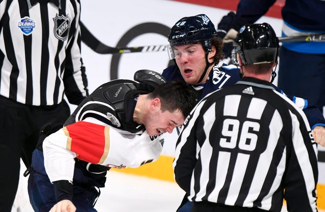 MacKenzie Weegar of the Florida Panthers, left, and Brendan Lemieux of the Winnipeg Jets fight on Friday.
