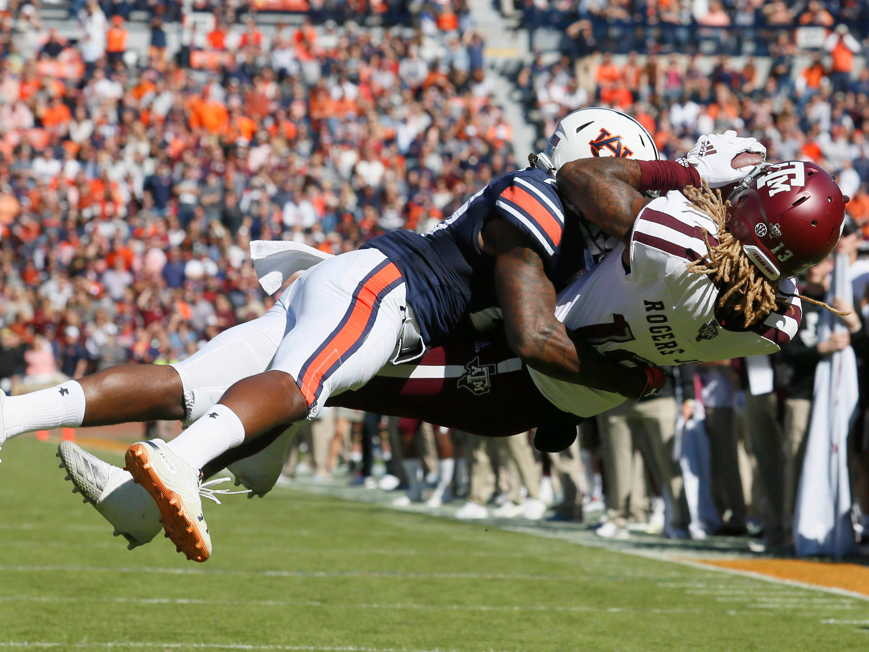Texas A&M Aggies receiver Kendrick Rogers (13) tries to hang on to this diving catch after taking a hit from Auburn Tigers defensive back Jeremiah Dinson (20) during the second quarter at Jordan-Hare Stadium.