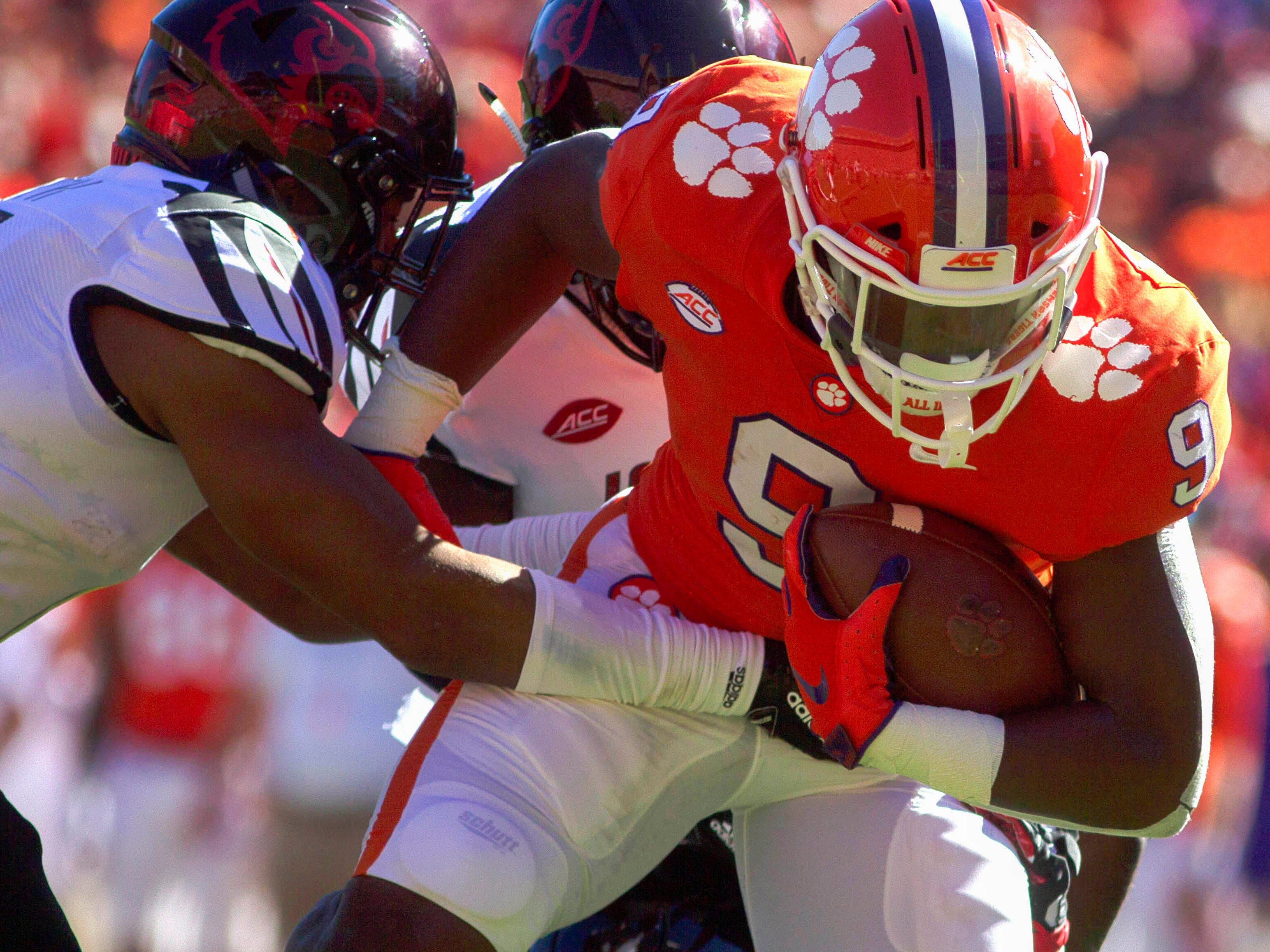 Clemson Tigers running back Travis Etienne breaks through tacklers to score a first-quarter touchdown against Louisville at Clemson Memorial Stadium.