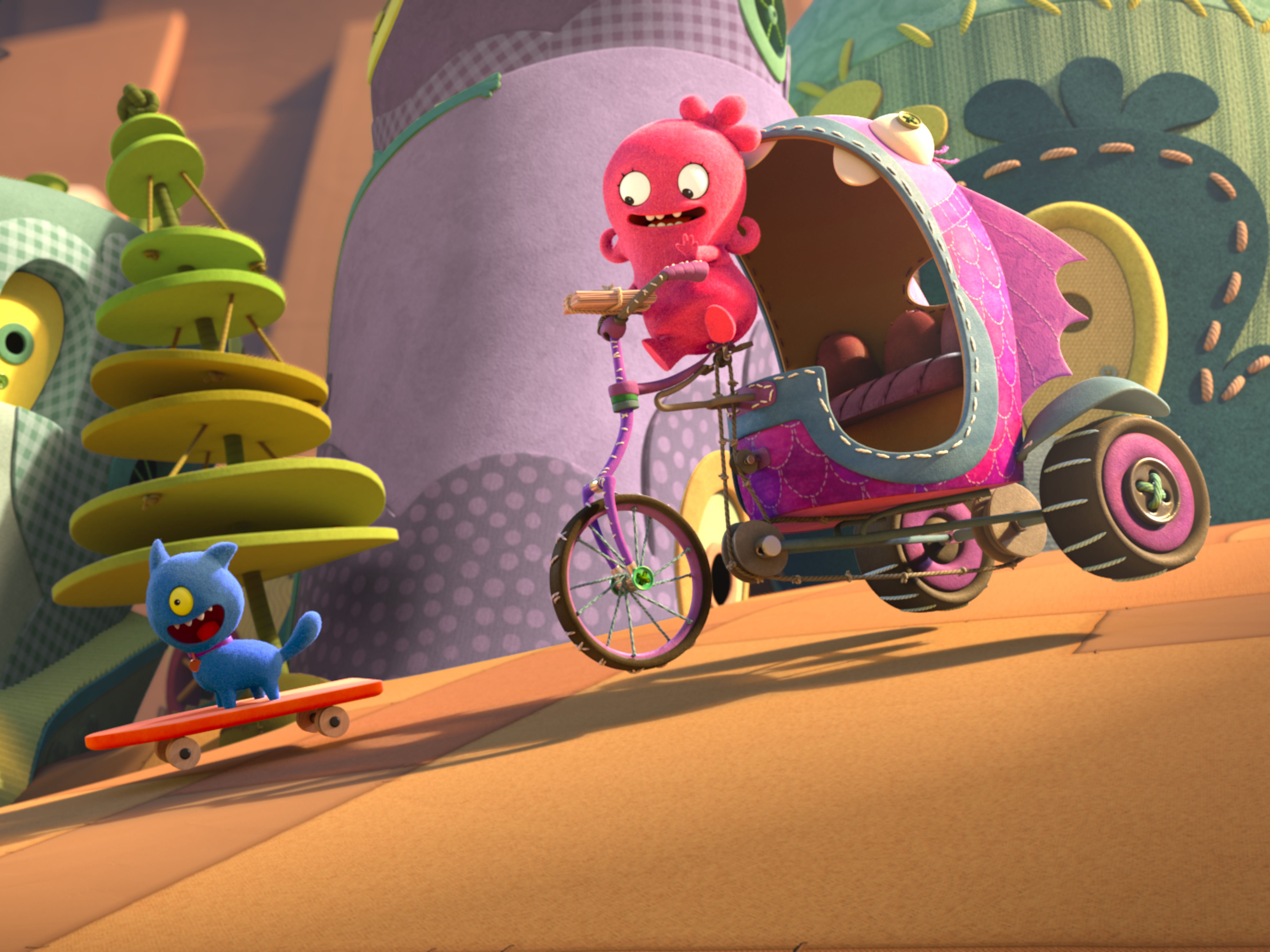 Moxy (voiced by Kelly Clarkson) rides her bike in Uglyville alongside Ugly Dog (Pitbull).