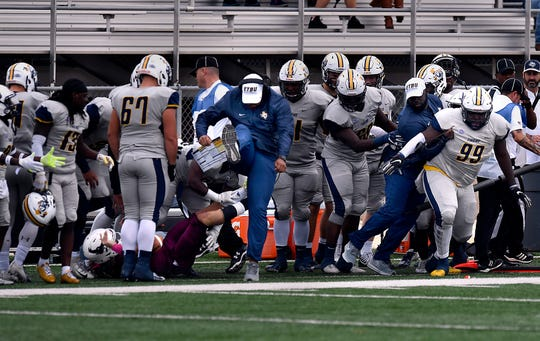 A coach on the opposing team kicks his leg in the air to avoid McMurry quarterback Kevin Hurley, jr. who was pushed to the ground by defensive lineman Khilan Wright after the play ended. The play drew a penalty against East Texas Baptist University during Saturday's game, Nov. 4, 2018.