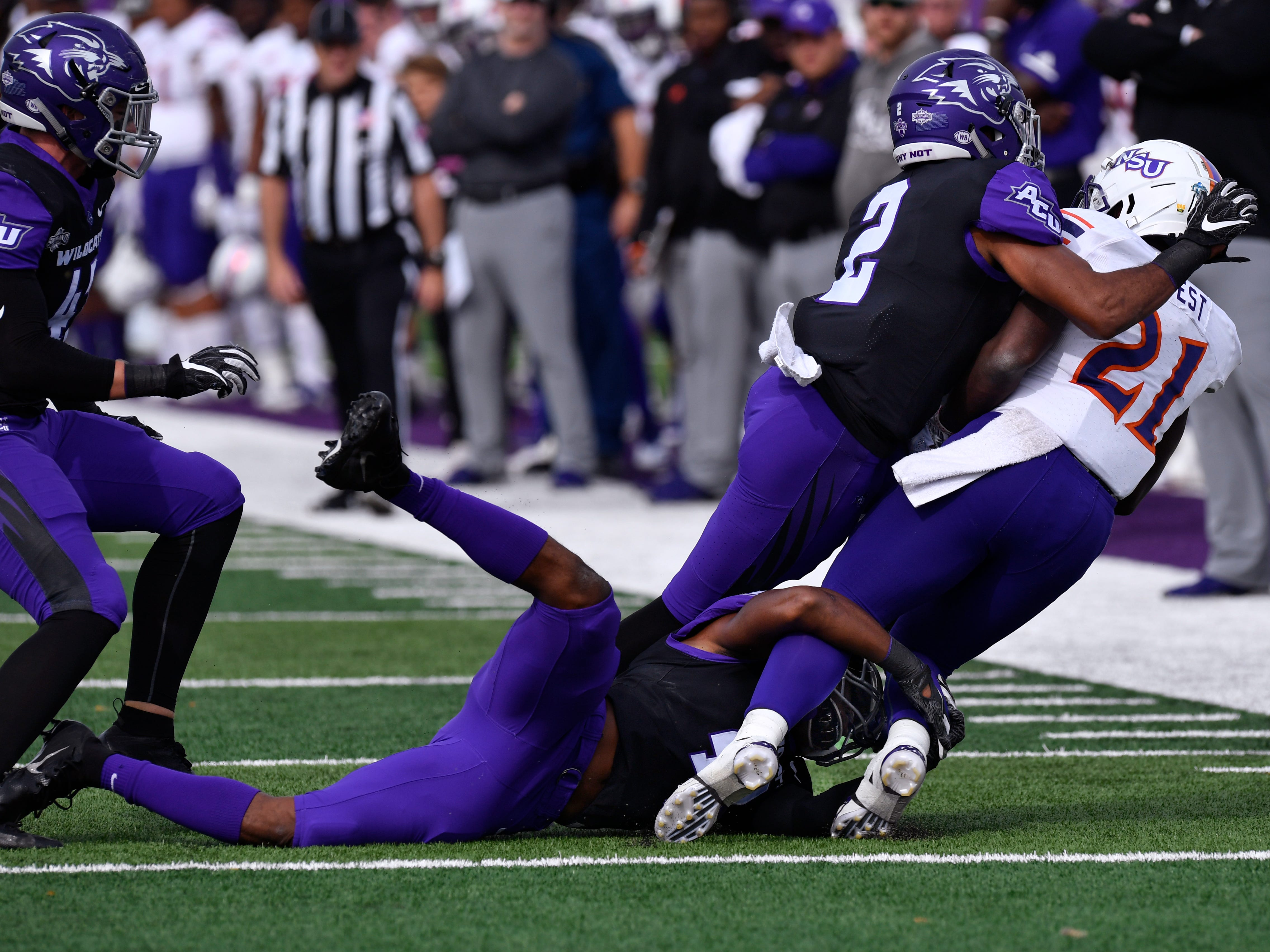 Wildcats' Alex Lofton grabs the legs of Northwestern State's Jared West while teammate Brandon Richmond finishes the job during Saturday's game Nov. 3, 2018.  Final score was 49-47, Abilene Christian University.
