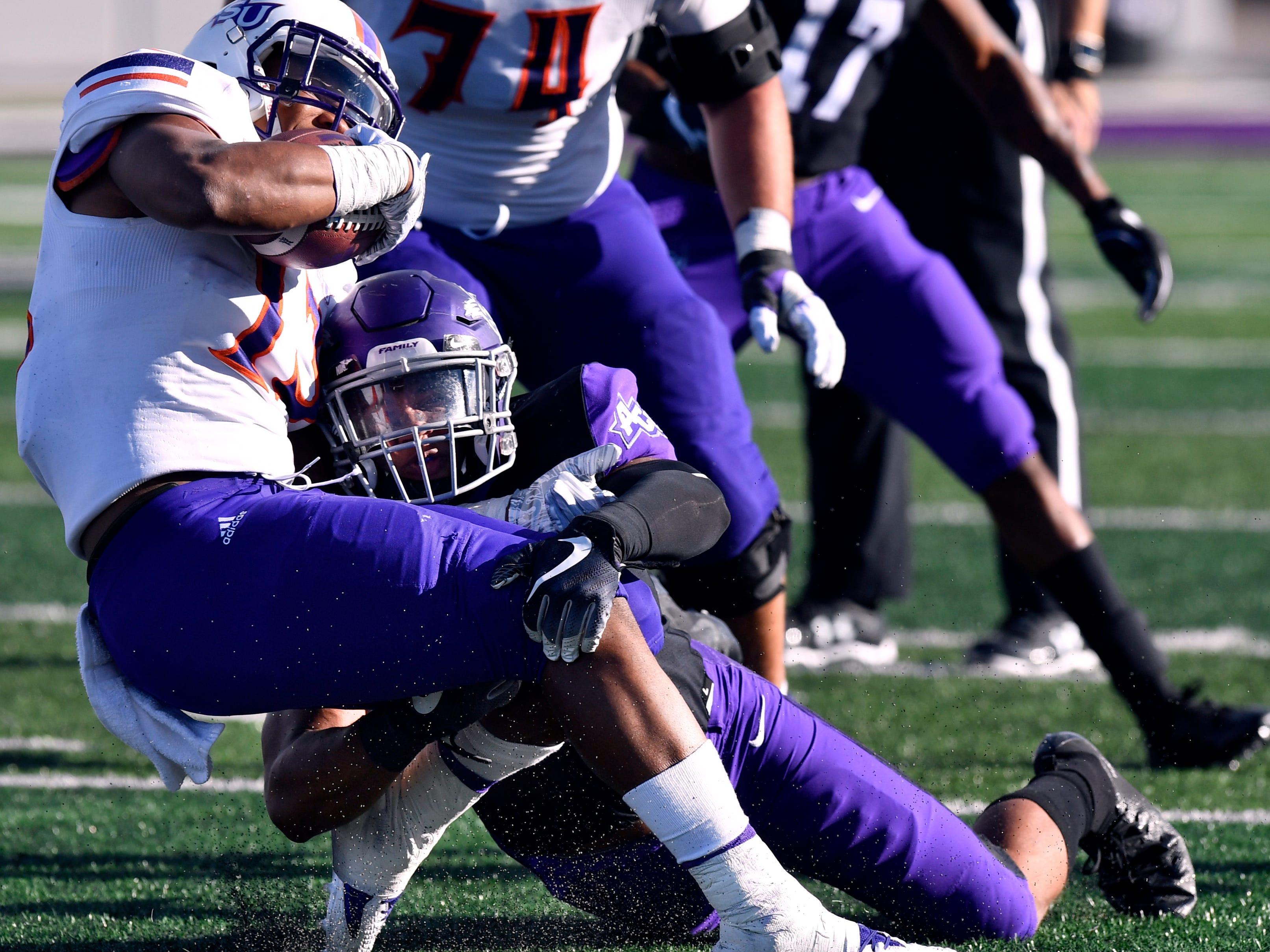 Abilene Christian linebacker Jeremiah Chambers tackles Northwestern State running back Stadford Anderson during Saturday's game Nov. 3, 2018. Final score was 49-47, Abilene Christian University.