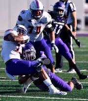 Abilene Christian linebacker Jeremiah Chambers, shown here tackling Northwestern State running back Stadford Anderson during a game last season, was named a third-team All-American by HERO Sports. Chambers finished his college career with ACU this season as a senior.