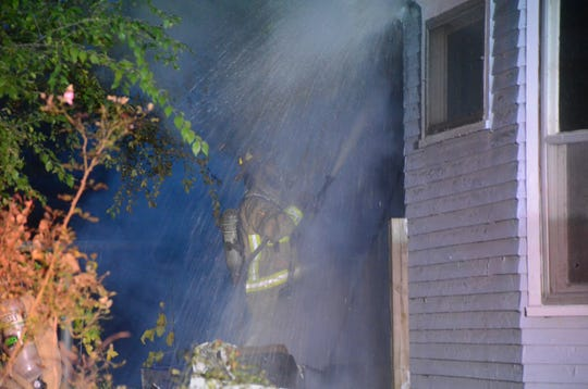 A firefighter battles the fire at the rear of the Post Addition home on Sunday.