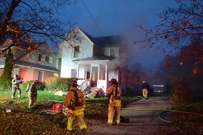 While others were already inside fighting the blaze, other Battle Creek firefighters gather at the front of the home at 396 Cliff St. Sunday.