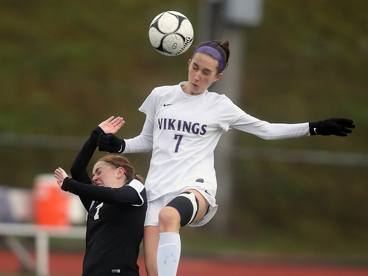 North Kitsap's Audrey Zinn (7) connects with a header over Sequim's Daisy Ryan at Silverdale Stadium on Saturday, November 3, 2018.