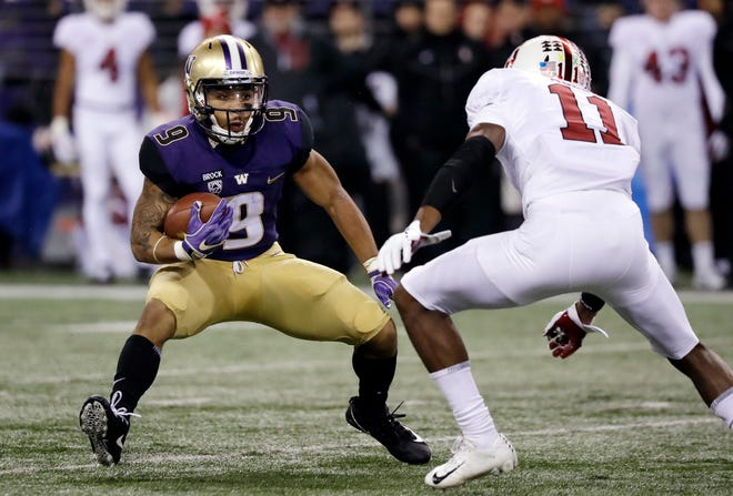 Washington's Myles Gaskin (9) carries as Stanford's Paulson Adebo moves in. Gaskin returned from a two-game absence for a season-best total of 148 rushing yards.