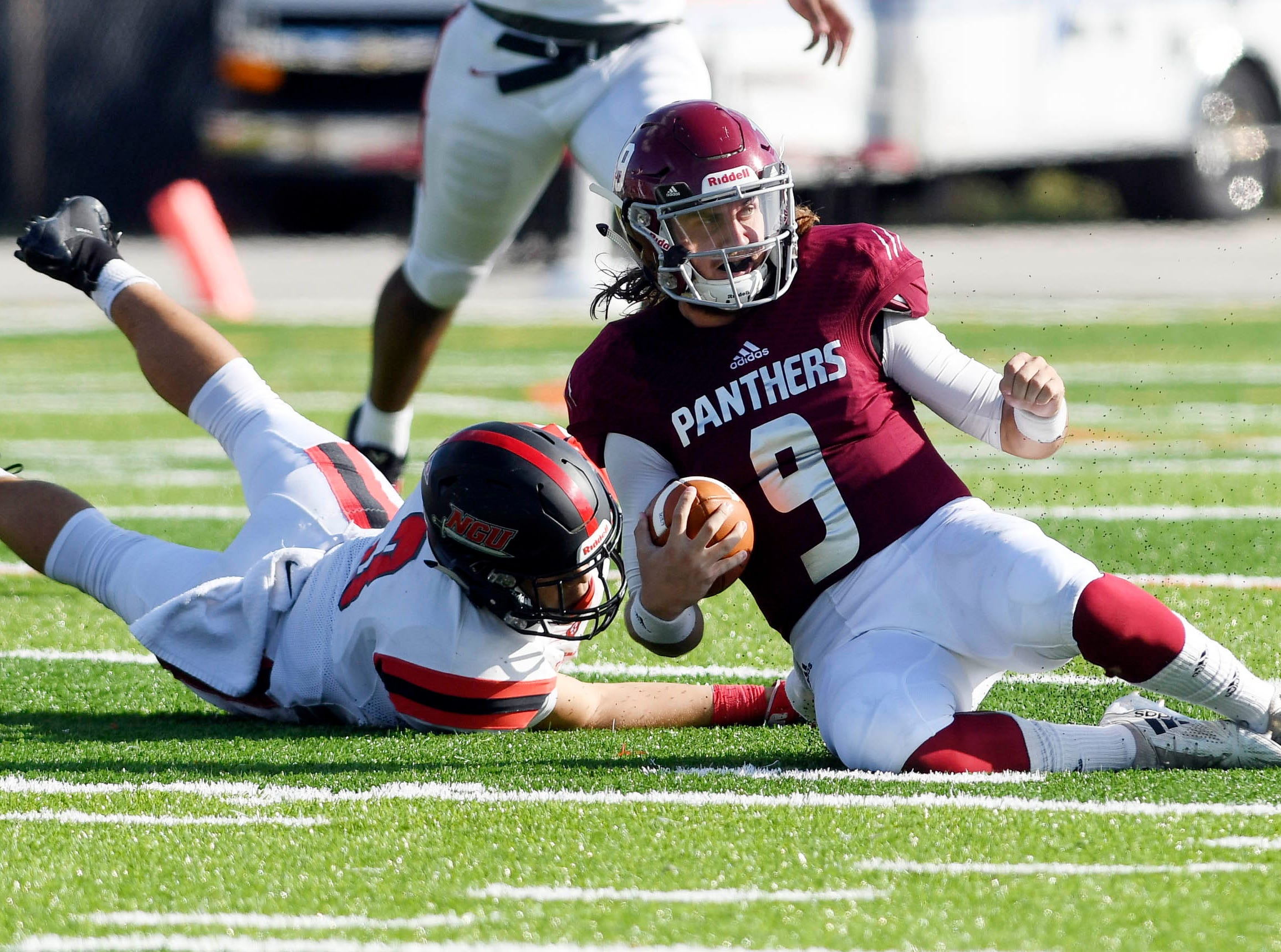Florida Tech QB Trent Chmelik slides to a stop before North Greenville's Matthew Thomas can make the tackle during Saturday's game.