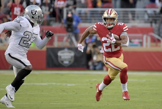San Francisco 49ers running back Matt Breida (22) runs against Oakland Raiders free safety Reggie Nelson (27) during the first half at Levi's Stadium.