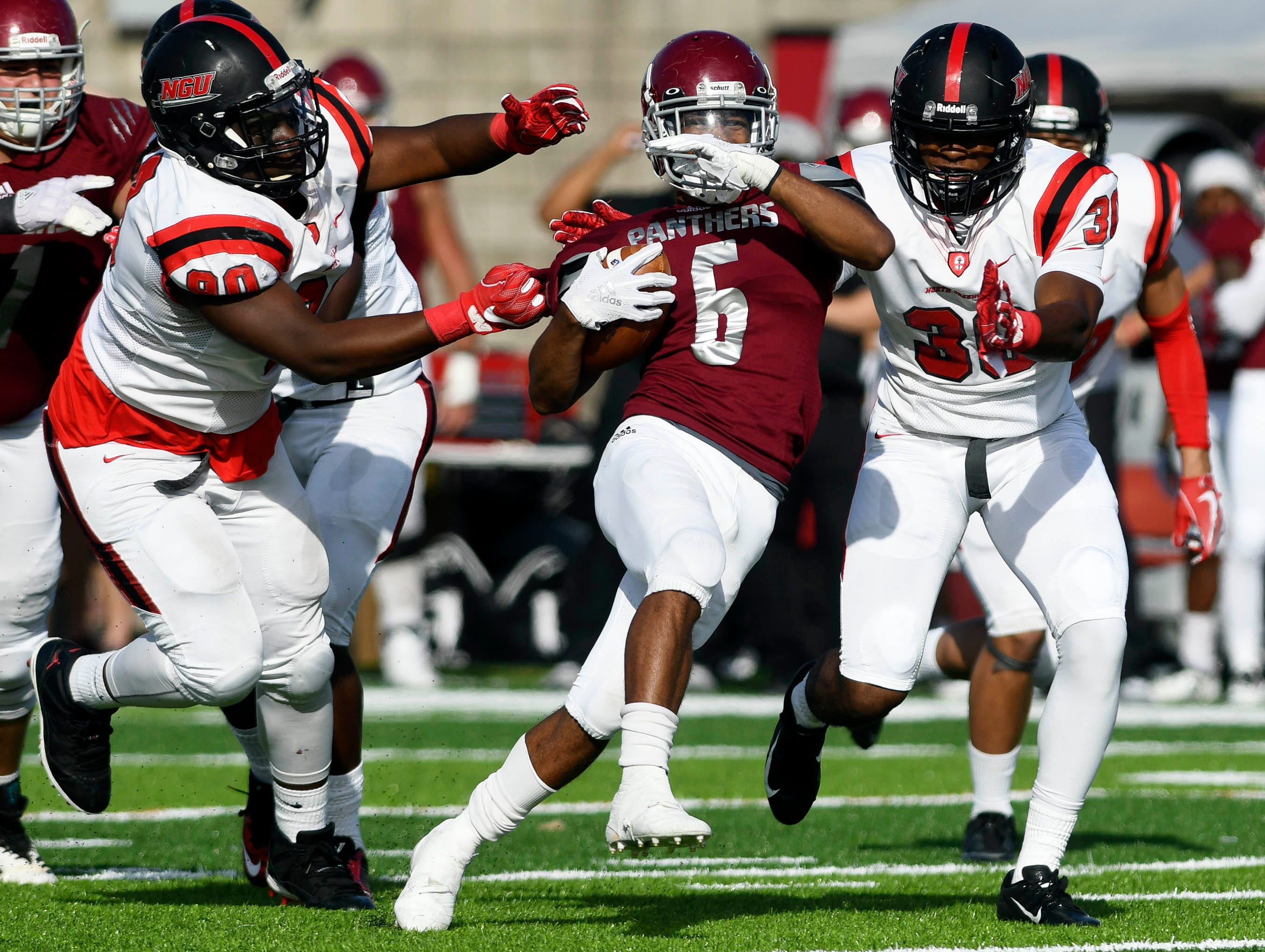 Antwuan Haynes of Florida Tech tries to fight through the tackle of Zeke Stringer (90) and Kendall Brooks (30) of North Greenville during Saturday's game.