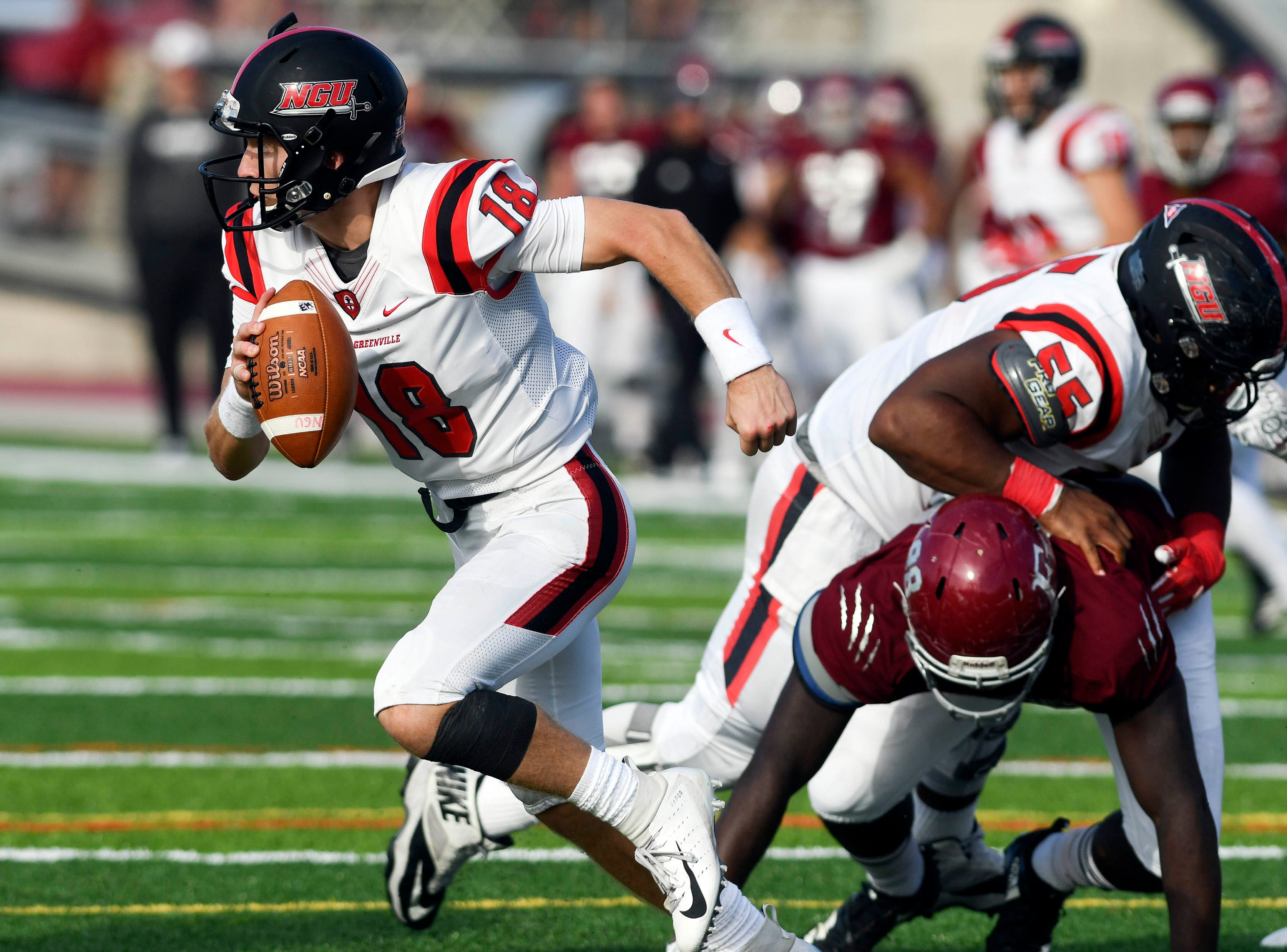 North Greenville QB Donnie Baker rolls away from the Florida Tech defensive rush during Saturday's game.