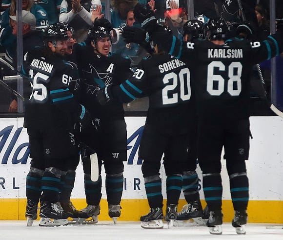 San Jose Sharks' Timo Meier, second from left, celebrates with Erik Karlsson (65) and Logan Couture (39) after scoring the game winning goal against the Philadelphia Flyers during overtime of an NHL hockey game Saturday, Nov. 3, 2018, in San Jose, Calif. At right is Sharks' Melker Karlsson (68) and Marcus Sorensen (20).