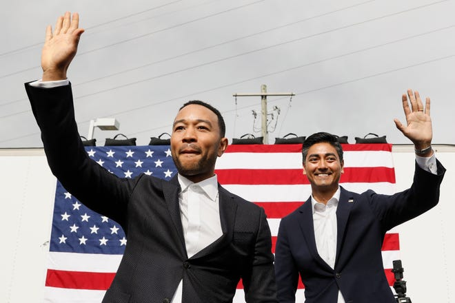 Recording artist John Legend and Hamilton County Clerk of Courts Aftab Pureval, the Democratic congressional candidate for Ohio's 1st District, wave to the crowd during an early voting campaign event, Sunday, Nov. 4, 2018, in Cincinnati. (AP Photo/John Minchillo)