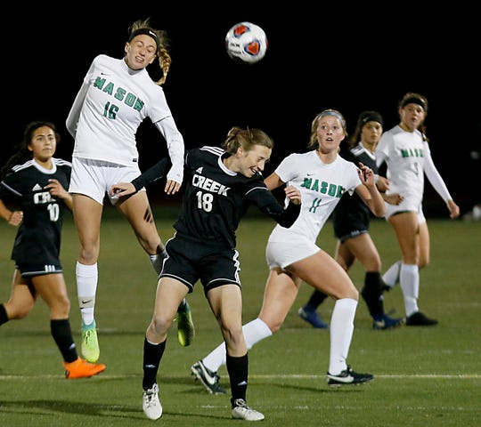Mason forward Kaitlyn Heckler heads the ball over Beavercreek forward Kaileigh Nuessgen during their girls soccer DI regional finals at Monroe Saturday, Nov. 3, 2018.