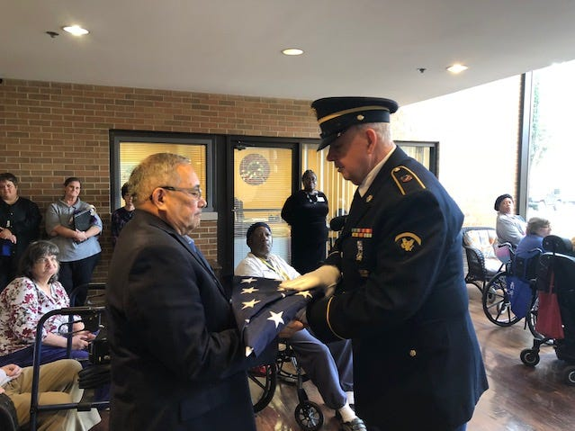 Color Guard Ray Frey of Green Township VFW Post 10380 hands the flag to Premier Estates at Norwood Towers exective director Manny Alverez. The post led a flag dedication ceremony and raised a new flag that now waves in front of Premier Estates.