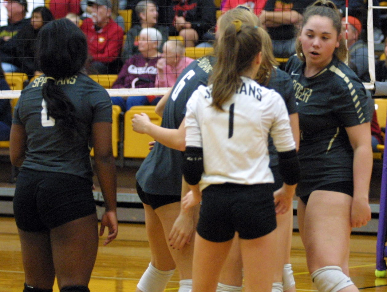 Roger Bacon players Olivia Berry (8), Olivia Hawkins (6) and Cammy Niesen (1) celebrate a point during their team's match against Bishop Fenwick in the regional final at Butler High School, Saturday, Nov. 3, 2018.