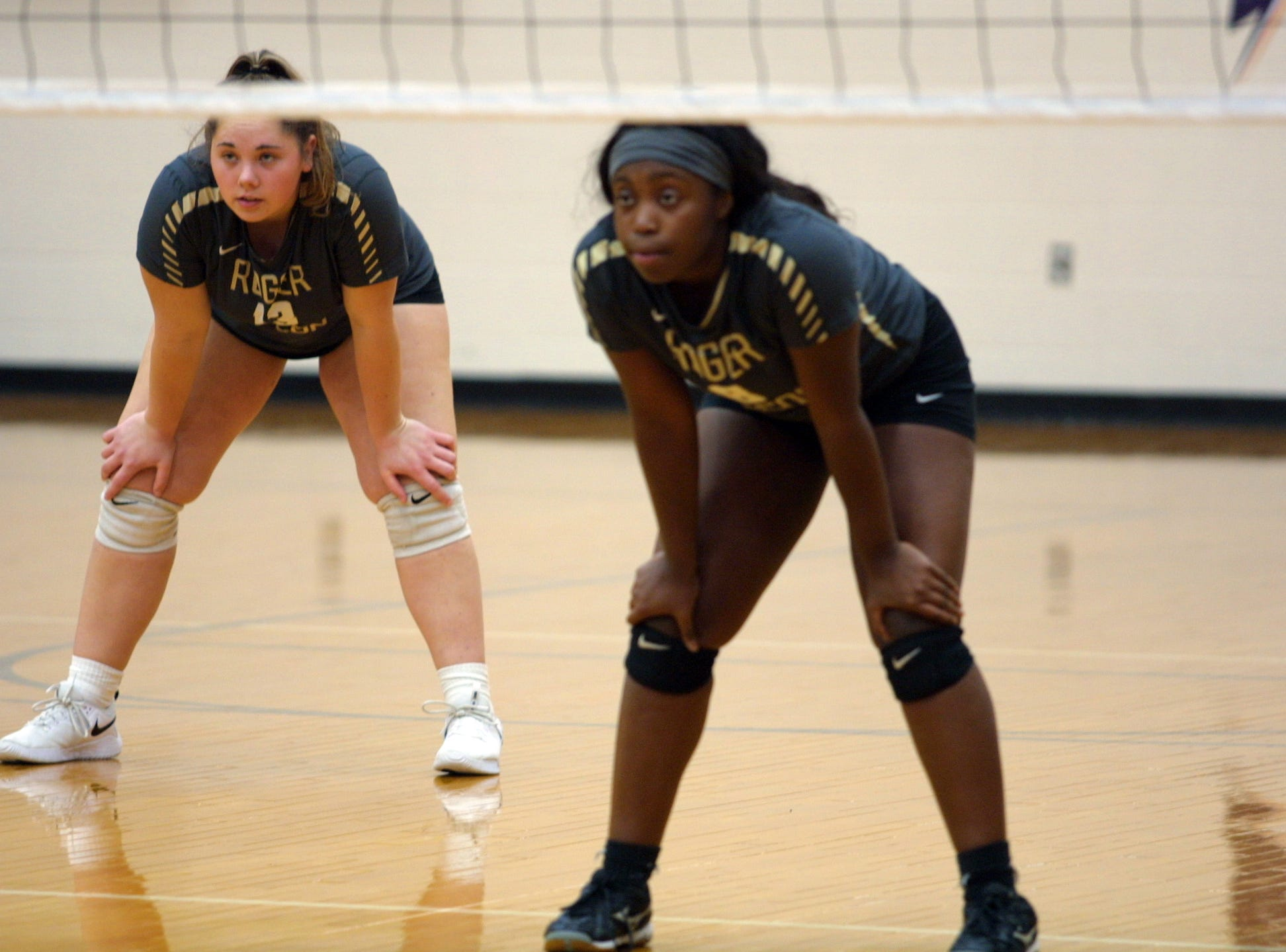 Roger Bacon players Haley Hoffman (13) and Olivia Berry (8) prepare for a return during their team's match against Bishop Fenwick in the regional final at Butler High School, Saturday, Nov. 3, 2018.