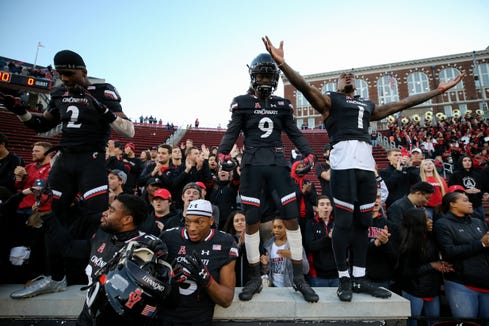 From left: Cincinnati Bearcats cornerback Tyrell Gilbert (2), Cincinnati Bearcats cornerback Arquon Bush (9) and Cincinnati Bearcats wide receiver Kahlil Lewis (1) celebrate the win during a college football game between the Navy Midshipmen and the Cincinnati Bearcats, Saturday, Nov. 3, 2018, at Nippert Stadium in Cincinnati.