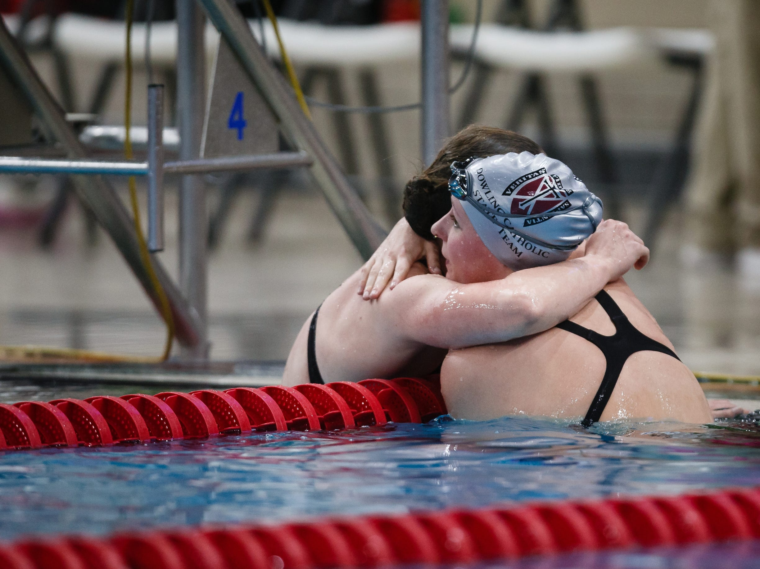 Dowling Catholic's Berit Quass, left, and teammate Claire Culver hug after swimming in the 500 yard freestyle at the Iowa girls state swimming meet on Saturday, Nov. 3, 2018, in Marshalltown.