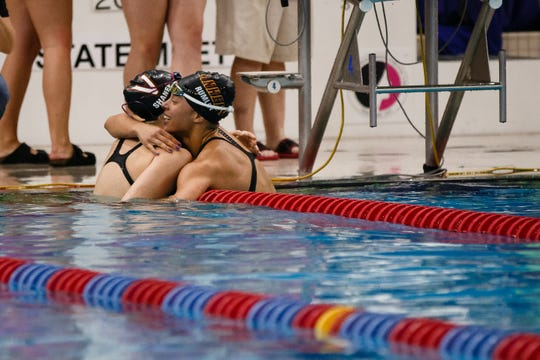 Jasmine Rumley from Ankeny, right, hugs Reilly Shaner of Valley after they competed in the 50 yard freestyle at the Iowa girls state swimming meet on Saturday, Nov. 3, 2018, in Marshalltown.