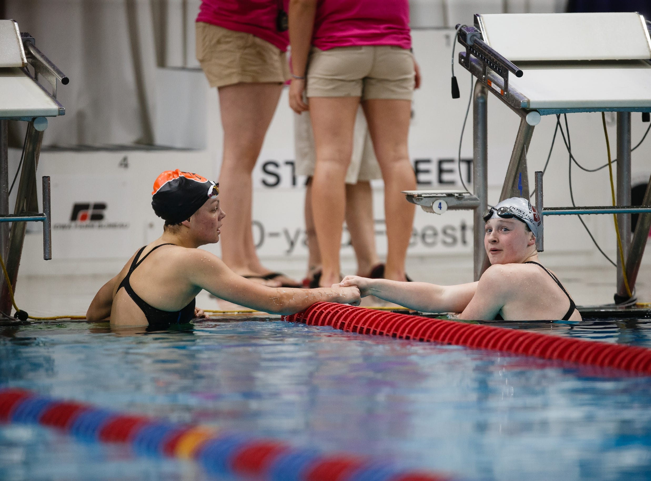 Dowling Catholic's Berit Quass congratulates Ames' Annie Galvin after they raced the 100 yard butterfly at the Iowa girls state swimming meet on Saturday, Nov. 3, 2018, in Marshalltown.