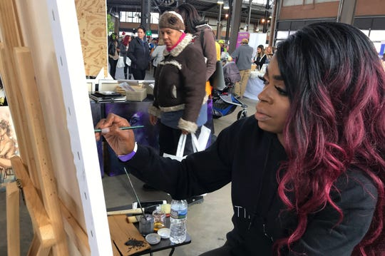 Artist Christina Madison, of Detroit, sells her paintings and creates a piece live at the All Things Detroit shopping experience at Eastern Market on Sunday, Nov. 4, 2018.