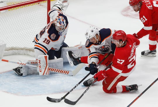 Oilers defenseman Matt Benning deflects the puck away from Red Wings center Michael Rasmussen in front of goaltender Mikko Koskinen during the third period Saturday in Detroit.