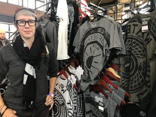 Bethany Shorb, owner of Well Done Goods, shows off their new Detroit man hole printed T-shirts at the All Things Detroit shopping experience at Eastern Market on Sunday, Nov. 4, 2018.