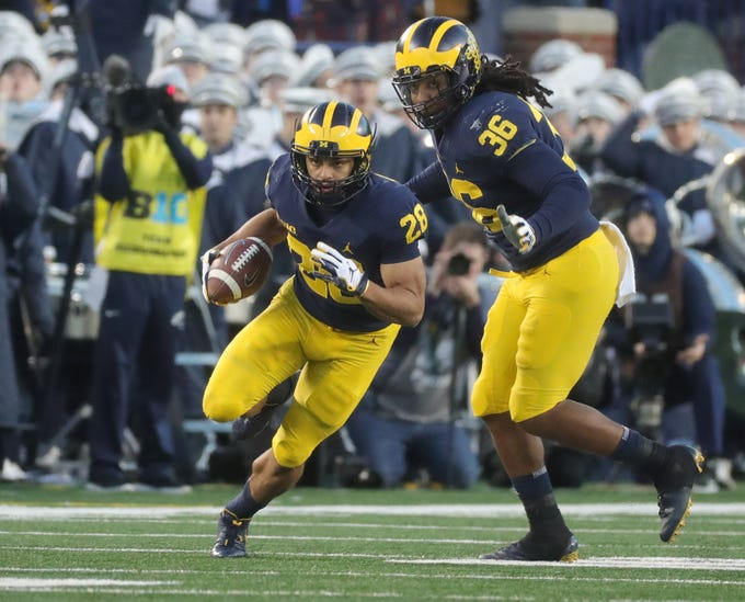 Michigan's Brandon Watson runs past teammate Devin Gil to return an interception 62 yards for a touchdown against Penn State in the second half Saturday, Nov. 3, 2018 at Michigan Stadium in Ann Arbor.