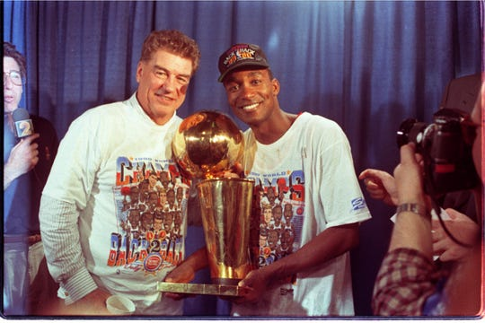 Detroit Pistons' coach Chuck Daly and player Isiah Thomas hold the 1990 NBA Championship trophy on June 14, 1990.