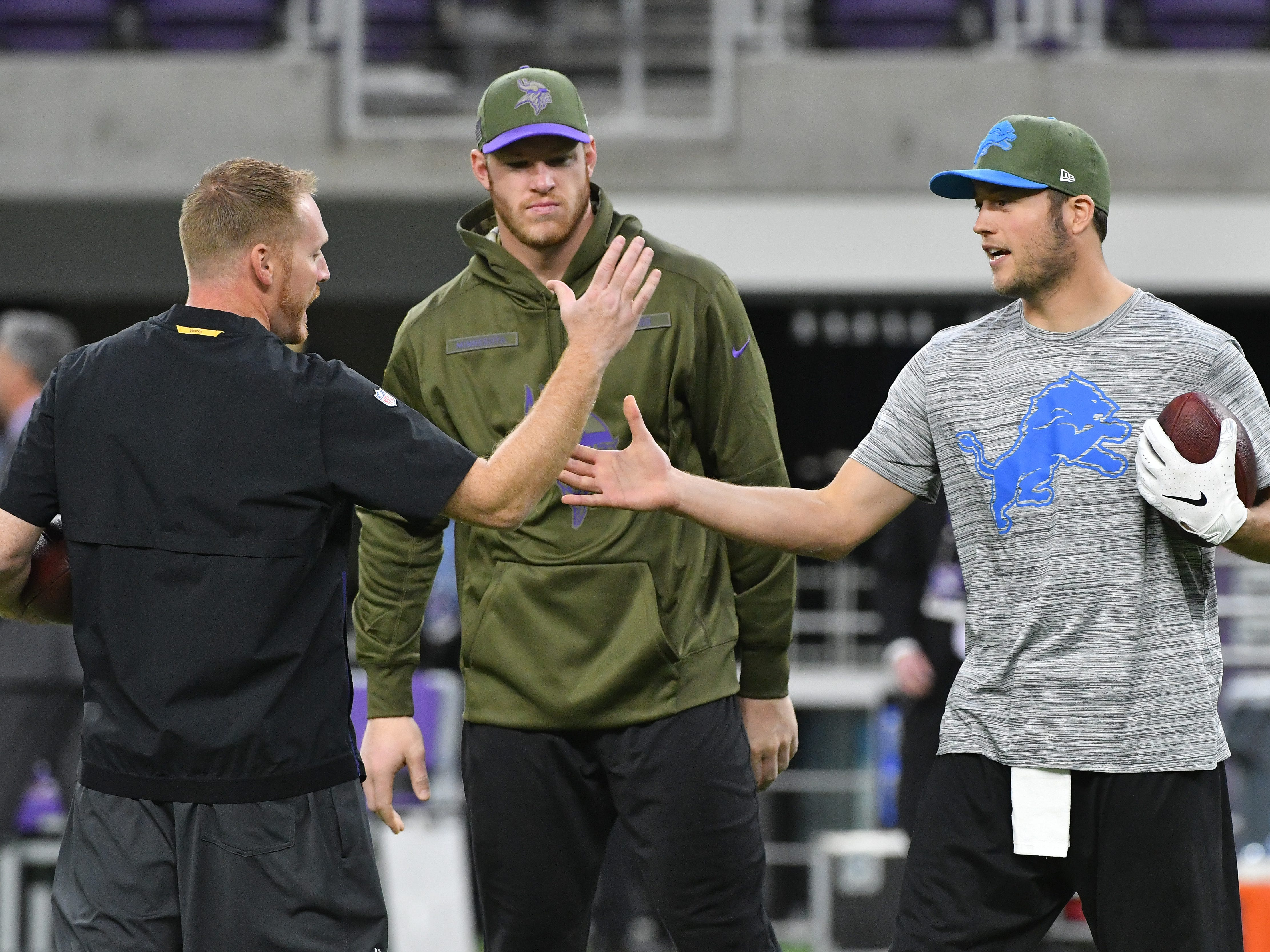 Former Lions quarterback coach Todd Downing, now tight ends coach with the Vikings and Minnesota tight end Kyle Rudolph catch up with Lions quarterback Matthew Stafford during warmups.