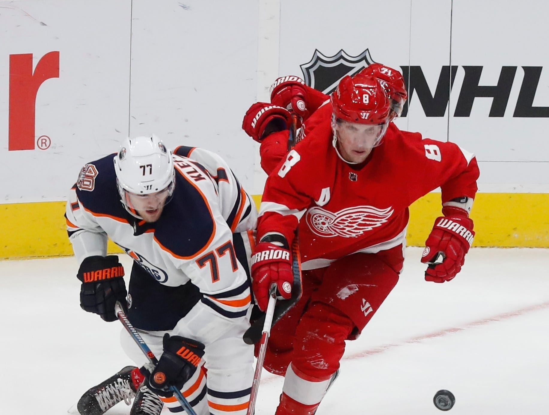 Edmonton Oilers defenseman Oscar Klefbom (77) and Detroit Red Wings left wing Justin Abdelkader (8) chase the puck during the third period of an NHL hockey game, Saturday, Nov. 3, 2018, in Detroit. Edmonton won, 4-3. (AP Photo/Carlos Osorio)