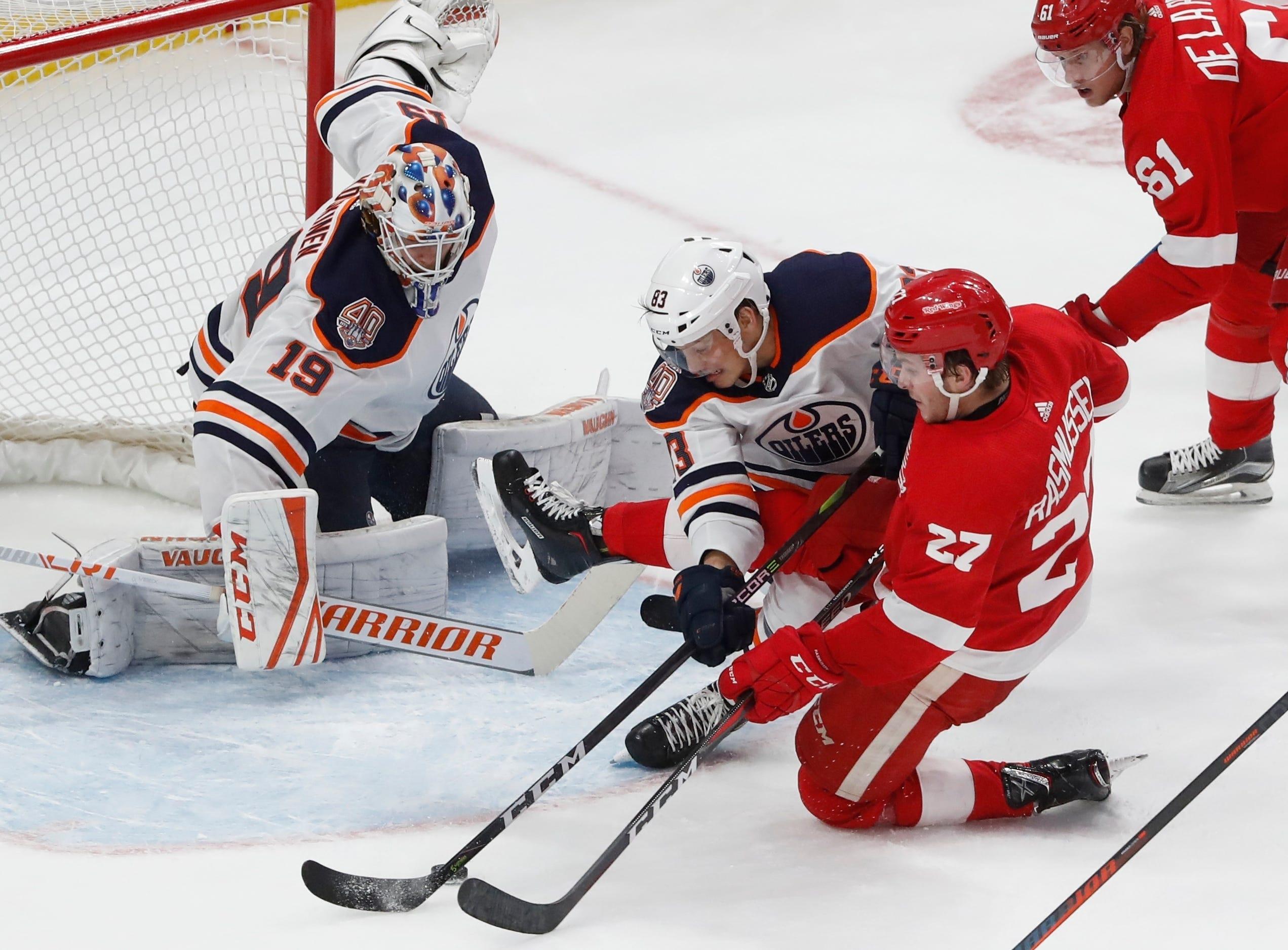 Edmonton Oilers defenseman Matt Benning (83) deflects the puck away from Detroit Red Wings center Michael Rasmussen (27) in front of goaltender Mikko Koskinen (19) during the third period of an NHL hockey game, Saturday, Nov. 3, 2018, in Detroit. Edmonton won, 4-3. (AP Photo/Carlos Osorio)