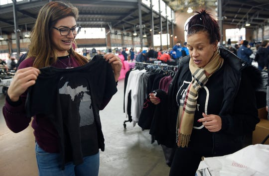 Marian Sandiha, 30, sales person for Ink Detroit shows Victoria Griffin, 48, of Detroit a t-shirt design at her booth during the event.** All Things Detroit is a marketplace for small businesses at Eastern Market. November 4, 2018, Detroit, MI.