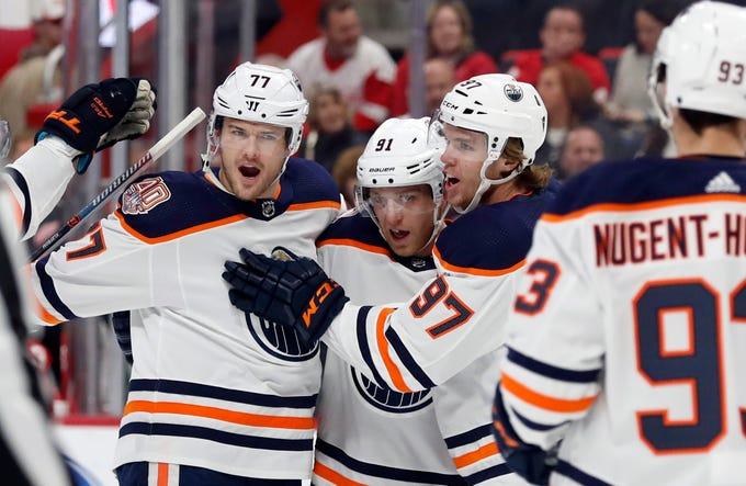 Edmonton Oilers left wing Drake Caggiula (91) is congratulated, after his goal, by teammates defenseman Oscar Klefbom (77), center Connor McDavid (97) and center Ryan Nugent-Hopkins (93) during the first period of an NHL hockey game against the Detroit Red Wings, Saturday, Nov. 3, 2018, in Detroit. (AP Photo/Carlos Osorio)