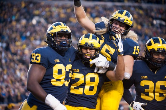 Michigan defensive back Brandon Watson (28) is mobbed in celebration by his teammates Lawrence Marshall (93), Chase Winovich (15) and Devin Gil (36) after he intercepted a pass and returned it 62 yards for a touchdown in the third quarter. The Wolverines' 42-7 victory over the Nittany Lions avenged a 42-13 loss at Penn State last year.