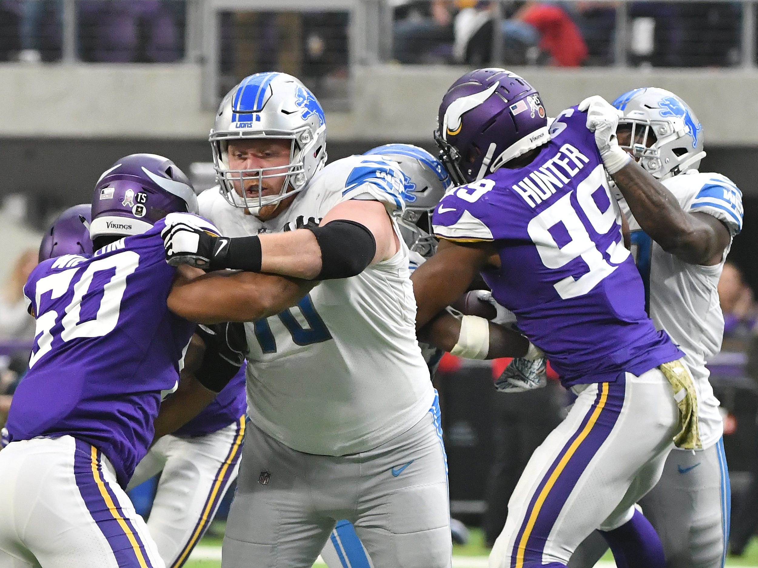 Lions' T.J. Lang defends against Vikings'  Eric Wilson in the second quarter.